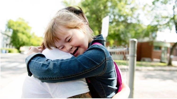 Abbraccio tra genitore e figlia down